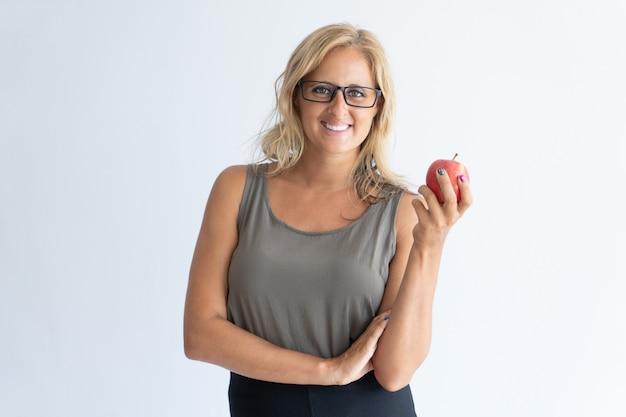 Retrato de feliz empresaria adulta media en vasos con manzana.