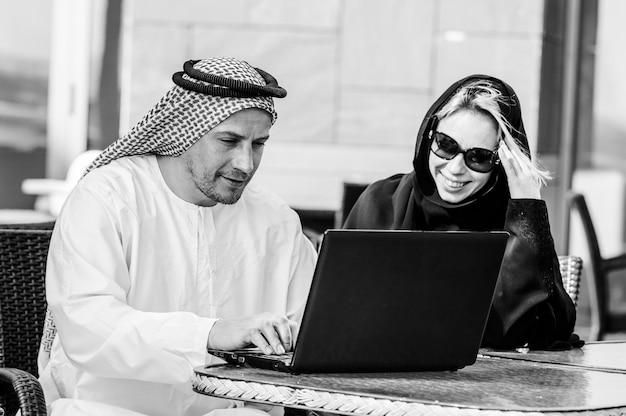 Retrato de feliz empresaria árabe y empresario en café tropical de verano. trabajo autónomo y a distancia. mujer árabe y pareja árabe enamorada trabajan juntos en la orilla