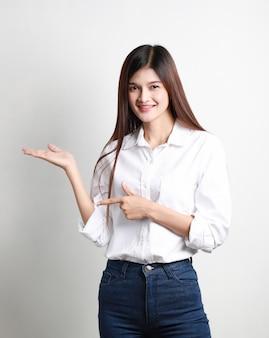 Retrato de feliz empresaria asiática joven posando aislada en la pared blanca, hermosa niña tailandesa sonriente apuntando hacia arriba, concepto de negocio.