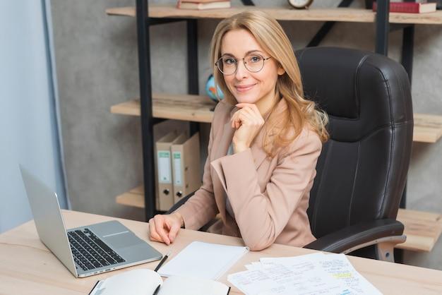 Retrato feliz de una empresaria joven sonriente que se sienta en silla en el lugar de trabajo con el ordenador portátil y los papeles en la tabla