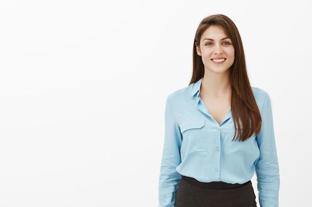 Retrato de feliz empresaria morena saliente posando en el estudio