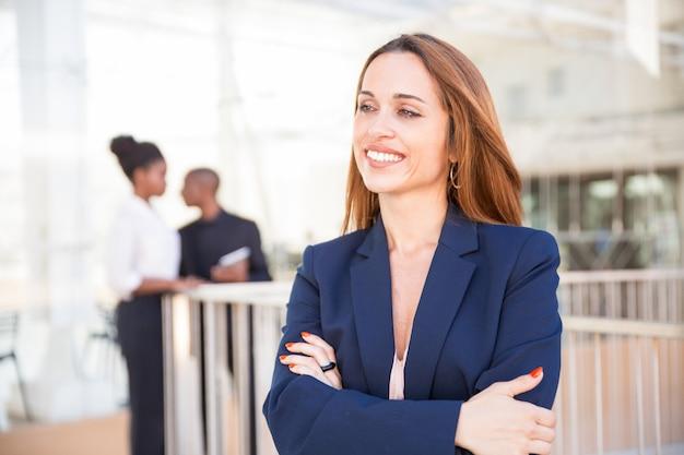 Retrato de feliz empresaria y sus empleados en segundo plano