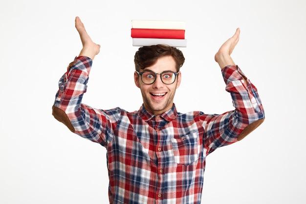 Retrato de un feliz estudiante emocionado sosteniendo libros