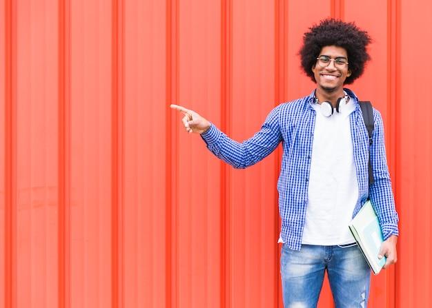 Retrato feliz de un estudiante masculino que señala su dedo que se opone a una pared brillante