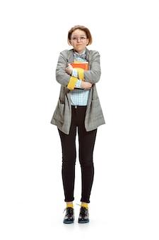 Retrato de una feliz estudiante sonriente sosteniendo libros aislados en pared blanca