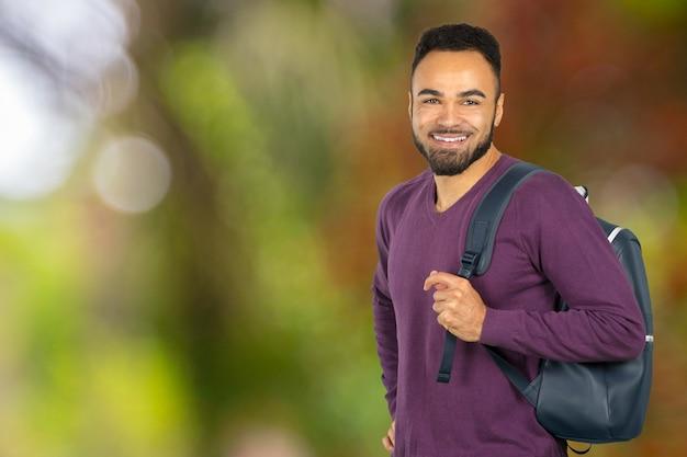 Retrato feliz del estudiante universitario aislado