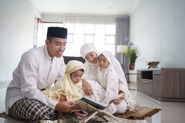 Retrato de feliz familia musulmana con niños leyendo el corán y orando juntos en casa