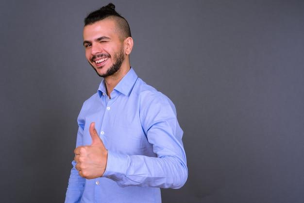 Retrato de feliz guapo empresario turco barbudo dando pulgares