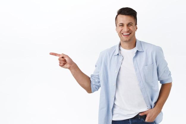 Retrato de feliz, guapo hombre adulto masculino apuntando con el dedo hacia la izquierda y sonriendo, recomendar servicio o producto