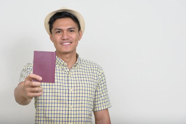 Retrato de feliz guapo turista asiático hombre mostrando pasaporte