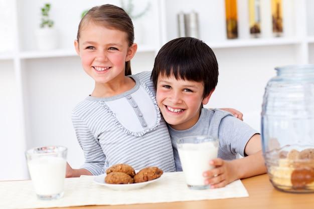 Retrato de feliz hermano y hermana comiendo galletas