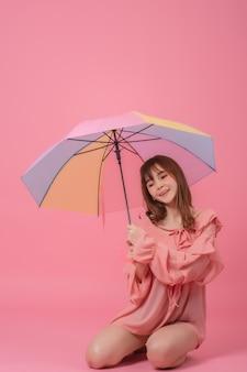 Retrato de feliz hermosa joven asiática sosteniendo paraguas, sonriendo en rosa