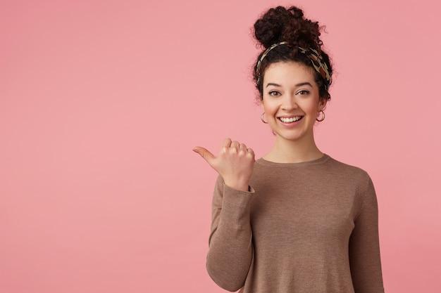Retrato de feliz hermosa joven con cabello oscuro y rizado, sonriendo ampliamente y mirando a la cámara y apuntando con el dedo para copiar el espacio aislado sobre fondo rosa.