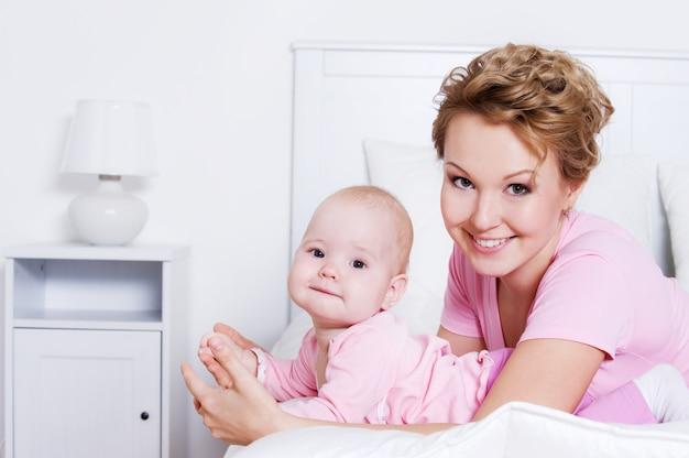 Retrato de feliz hermosa joven madre acostada con su bebé en la cama