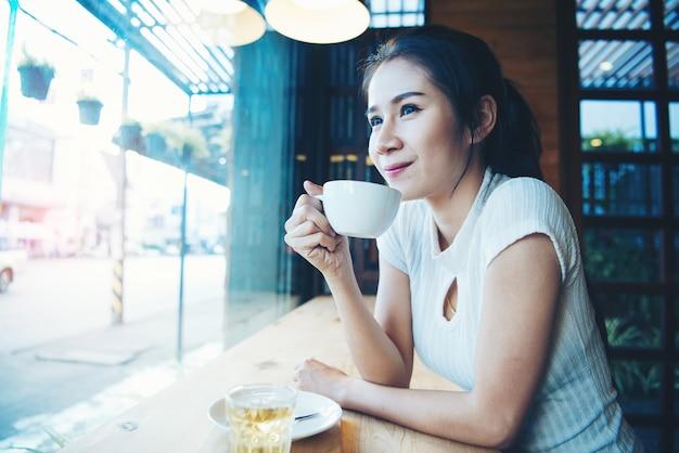 Retrato de feliz hermosa mujer con taza en las manos
