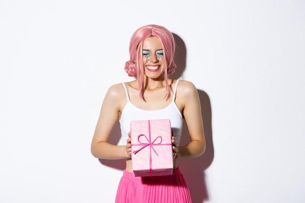 Retrato de feliz hermosa niña b-day mirando emocionada, recibiendo regalo de cumpleaños y sonriendo con alegría, de pie con peluca rosa y traje de fiesta.