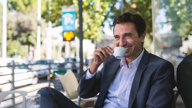Retrato feliz del hombre de negocios de la edad media que bebe un café al aire libre en roma, italia.