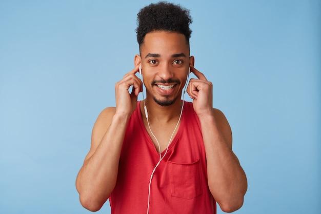 Retrato de feliz joven afroamericano tiene las manos en los auriculares, escucha canciones geniales, viste una camiseta roja, mira y se para.