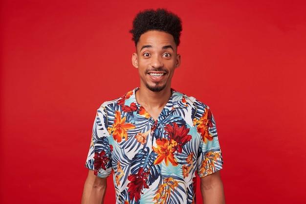 Retrato de feliz joven afroamericano, viste con camisa hawaiana, mira a la cámara con expresión alegre, se encuentra sobre fondo rojo y sonríe ampliamente.