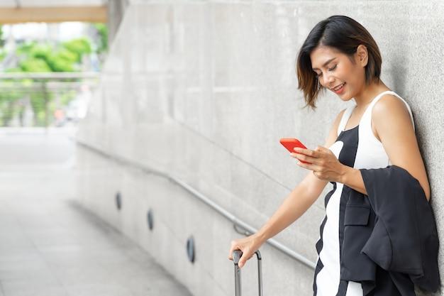 Retrato feliz joven y bella mujer de pie cerca de la pared sonriendo y uso smartphone
