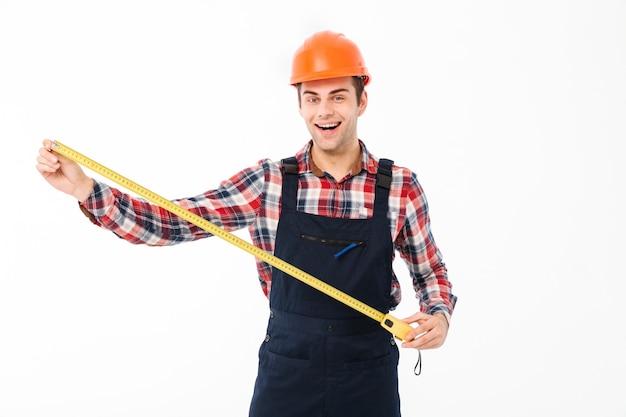 Retrato de un feliz joven constructor masculino mostrando