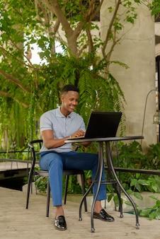 Retrato de feliz joven empresario africano vistiendo ropa casual y sentado en la cafetería mientras usa una computadora portátil y distanciamiento social