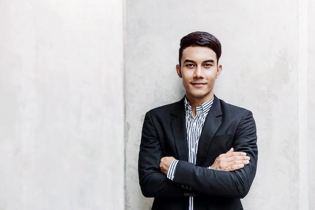 Retrato de feliz joven empresario de pie en la pared, sonriendo y cruzó los brazos