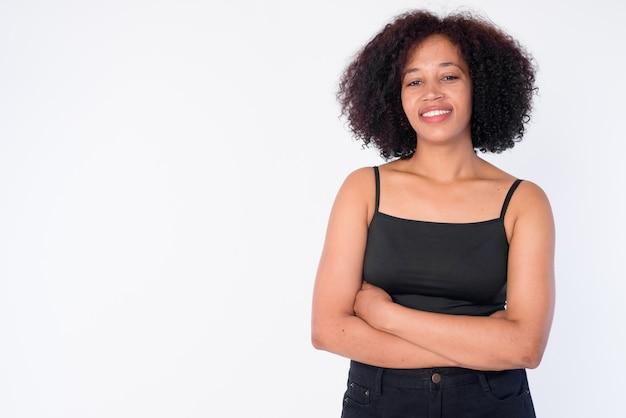 Retrato de feliz joven hermosa mujer africana sonriendo con los brazos cruzados