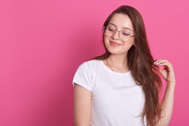 Retrato de feliz joven linda chica de cabello castaño sonriendo y mirando a un lado, toca el cabello, posando aislado en rosa