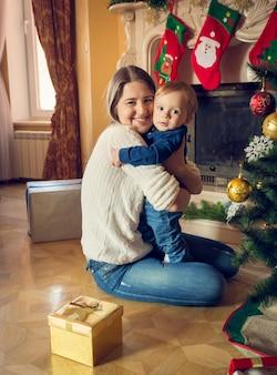 Retrato de feliz joven madre abrazando a su bebé de 1 año en el árbol de navidad