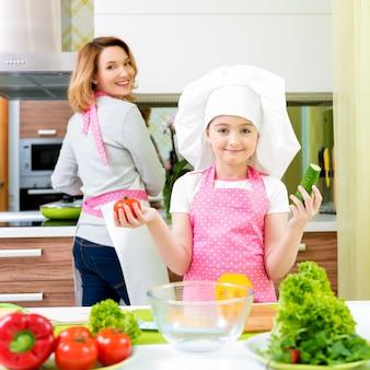 Retrato de feliz joven madre con hija en delantal rosa cocinando en la cocina.