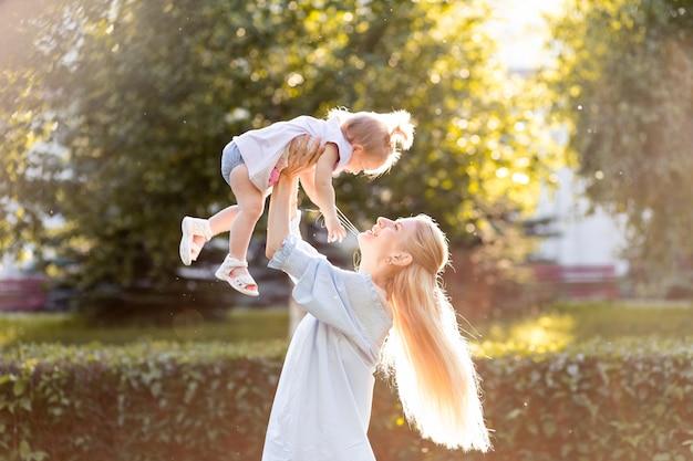Retrato de feliz joven madre con hijita linda