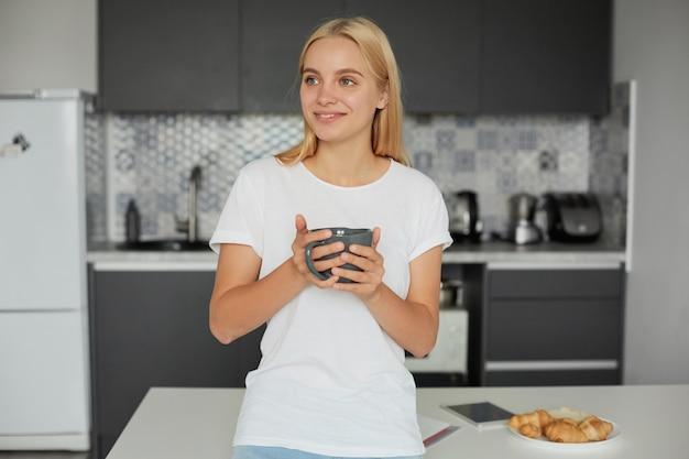 Retrato de feliz joven mujer rubia de buen humor se inclina sobre la mesa, sonriendo