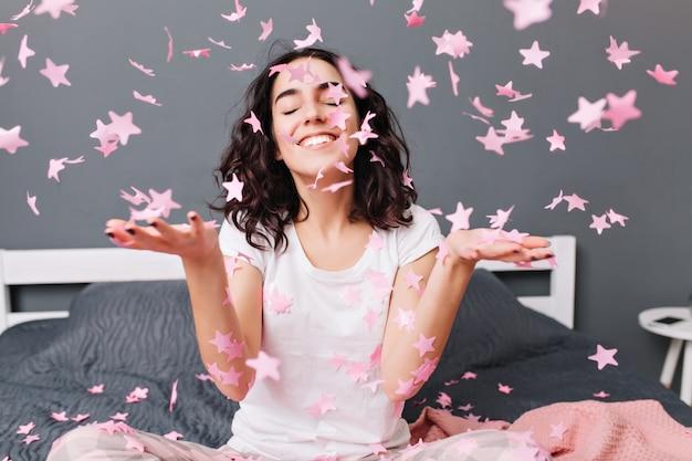 Retrato feliz joven en pijama escalofriante, sonriendo con los ojos cerrados en la caída de oropel rosa en la cama en el apartamento moderno. relájate, expresa felicidad, verdaderas emociones positivas.