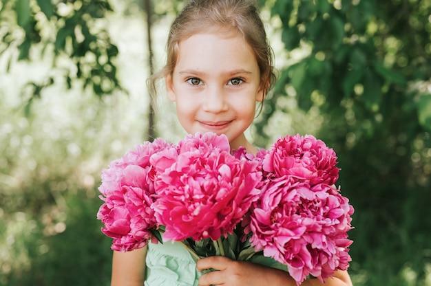 Retrato de una feliz linda niña caucásica de siete años, sostiene en las manos un ramo de flores de peonía rosa en plena floración en el fondo verde de la naturaleza