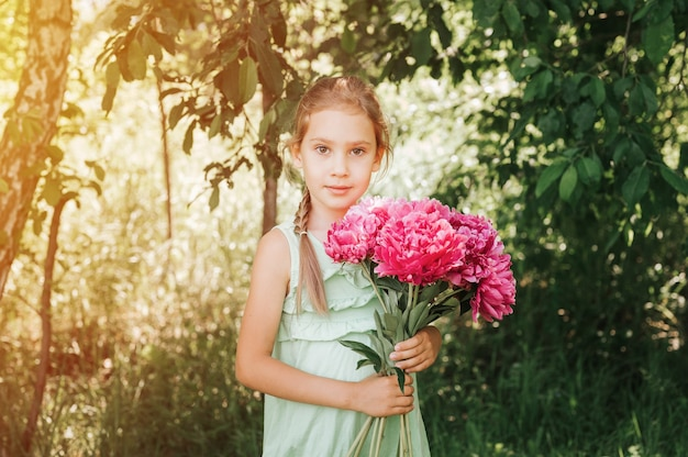 Retrato de una feliz linda niña caucásica de siete años en vestido de verano verde claro, sostiene en las manos un ramo de flores de peonía rosa en plena floración en el fondo de la naturaleza. llamarada