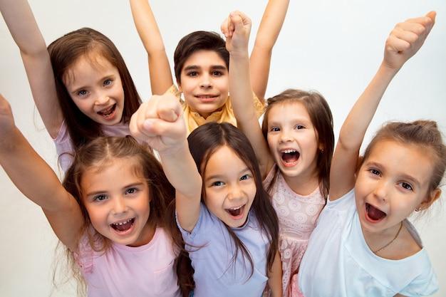 El retrato de feliz lindo niño y niñas en ropa casual con estilo. concepto de moda infantil y emociones humanas.