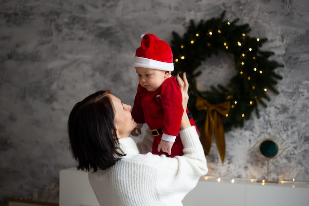 Retrato de feliz madre y adorable bebé celebran la navidad. vacaciones de año nuevo.