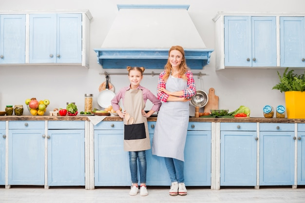 Retrato de feliz madre e hija en delantal de pie en la cocina