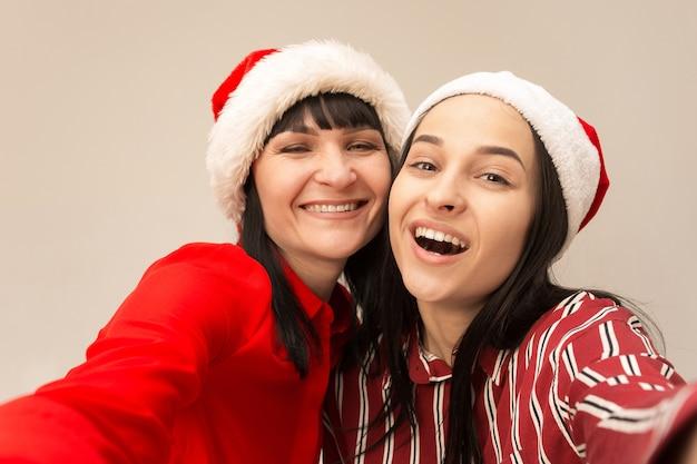 Retrato de una feliz madre e hija con sombrero de santa en estudio sobre fondo gris. concepto de expresiones faciales y emociones positivas humanas