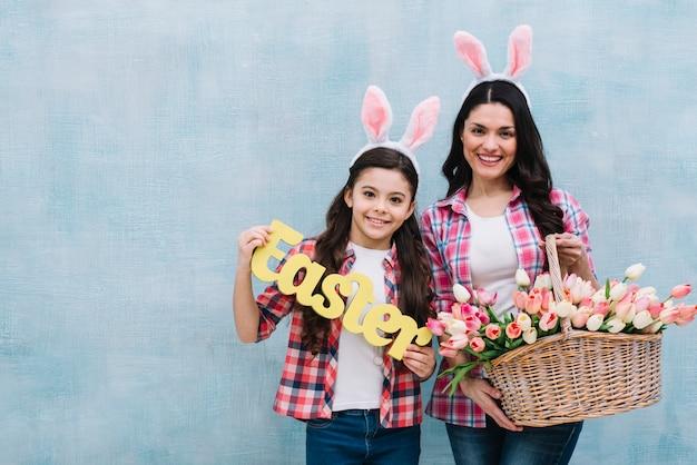 Retrato feliz de la madre y la hija que sostienen la palabra de pascua y la cesta de los tulipanes contra la pared azul