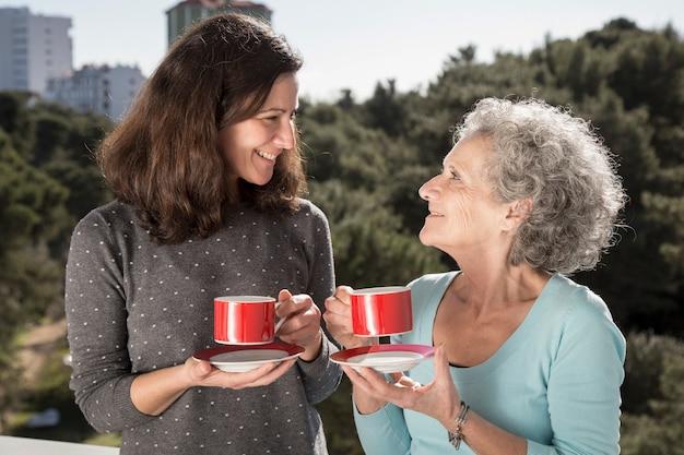 Retrato de feliz madre senior y su hija bebiendo té