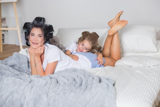 Retrato de la feliz madre y su pequeña hija en rizadores para el cabello. feliz madre e hija divirtiéndose en la cama en pijama.