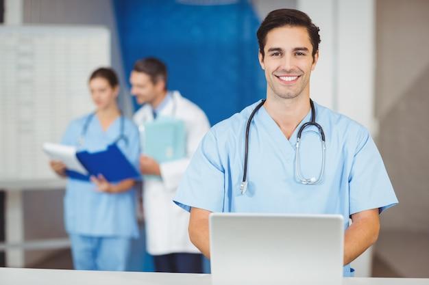 Retrato de feliz médico con laptop y colegas discutiendo