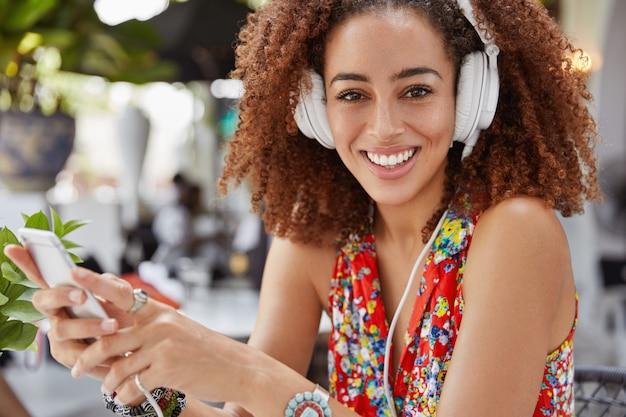 Retrato de feliz modelo femenino encantado de piel oscura posa contra el interior de la cafetería al aire libre con teléfono móvil