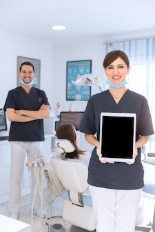 Retrato de feliz mujer dentista mostrando tableta digital en clínica