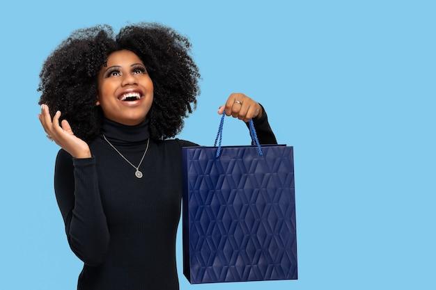 Retrato, de, un, feliz, mujer joven, con, grande, sonrisa, mirar hacia arriba, tenencia, bolsa de compras, azul, blackgraund