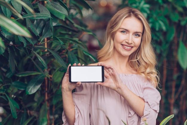 Retrato feliz de una mujer joven rubia que se coloca cerca de las plantas verdes que muestran la exhibición del teléfono móvil