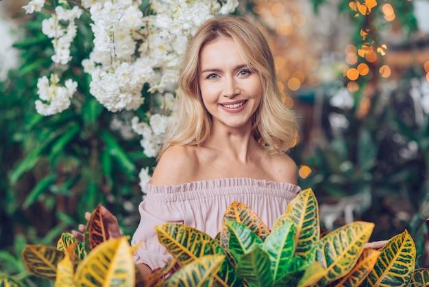 Retrato feliz de una mujer joven rubia que se coloca delante de las hojas amarillas y verdes