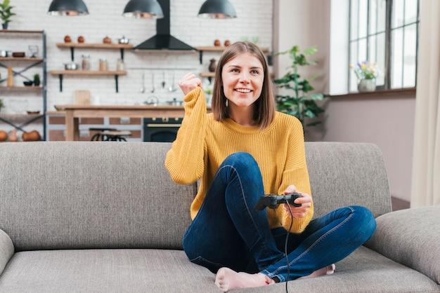 Retrato feliz de una mujer joven sonriente que se sienta en el sofá que juega al videojuego